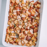 garlic and thyme potatoes in a white baking dish on a white table