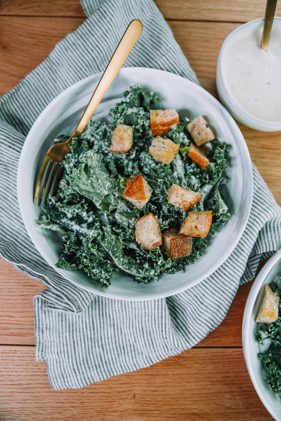 Kale Caesar Salad with fresh baked croutons in a white bowl on a wood table with a kitchen towel. Kale Caesar salad recipe by Farmer's Market Society.  Market Inspired Meals.