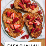 Thick slices of french toast with strawberries on a white plate.