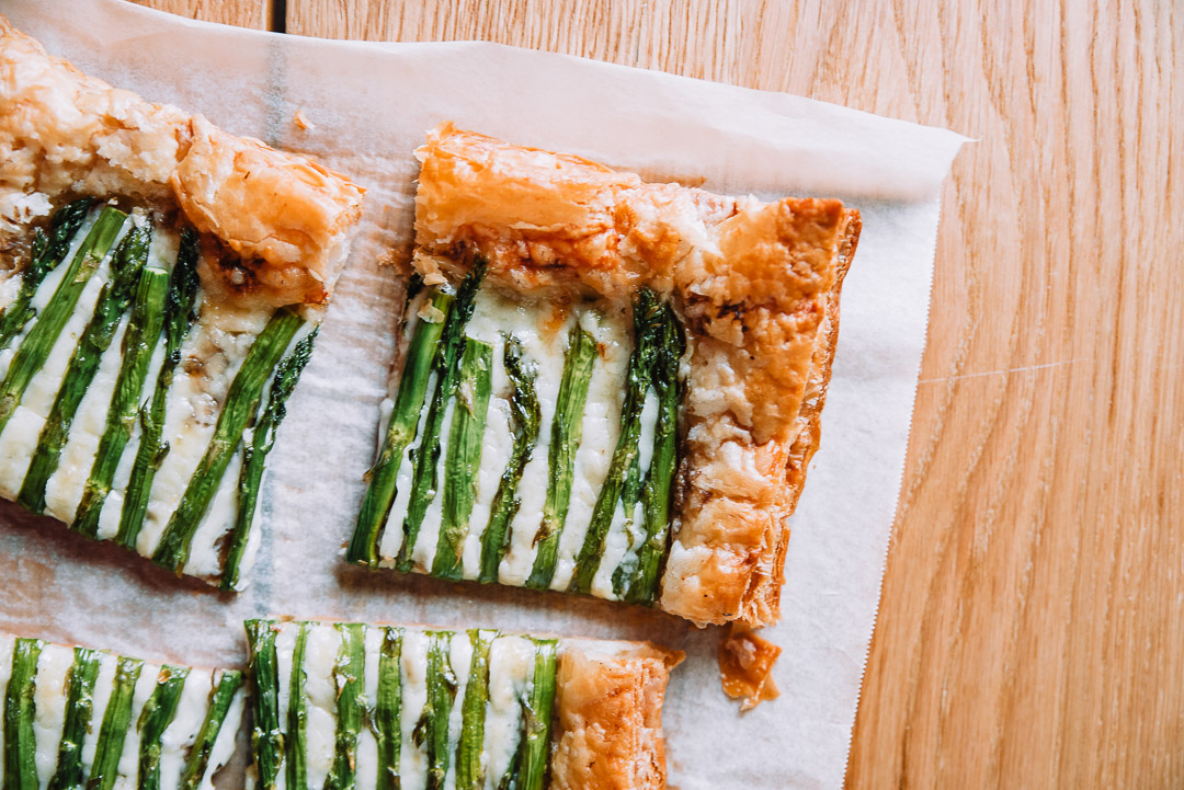 Spring asparagus tart on white parchment paper on wood table
