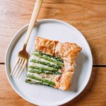 Spring Asparagus Tart on white plate with gold fork