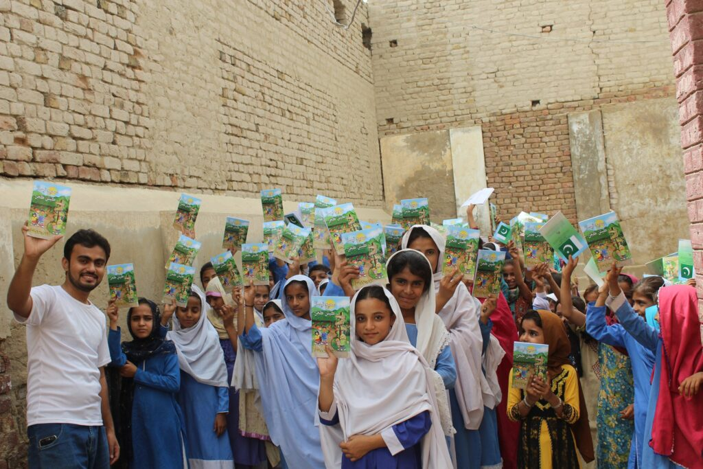 large group of Pakistan kids holding copies of the Way to Happiness.