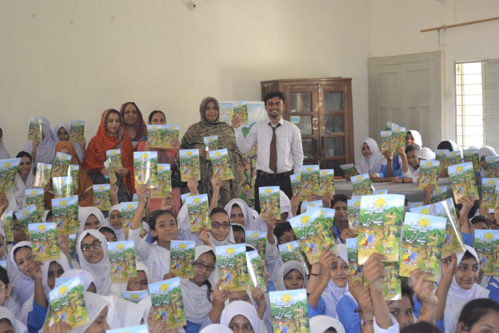 Teacher in Pakistan with classroom full of girl students, holding up Way to Happiness booklets