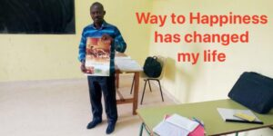 Tiade a teacher in Ivory Coast holding Way To Happiness poster, Happiness and Self Improvement