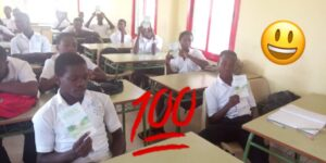 students of Tiade's holding Way to Happiness books in Ivory Coast class room, Happiness and Self Improvement