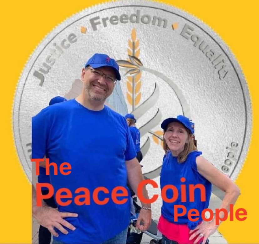 image of Chris and Kelly Watkins the Peace Coin people in front of a silver coin