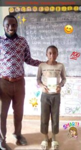 teacher standing with student holding the way to happiness book, chalk board holds way to happiness program, Happiness and Self Improvement