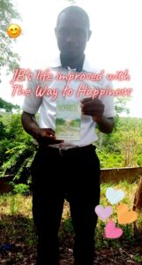 young man holds the way to happiness booklet in Siera Leone