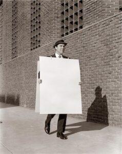 1950s BUSINESSMAN WALKING SIDEWALK WEARING ADVERTISING SANDWICH BOARD