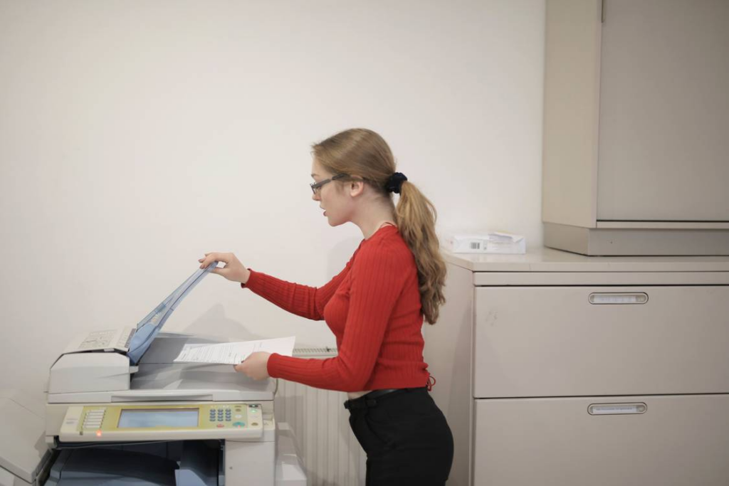 a female employee copying documents using the office copier.