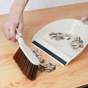 brush and broom sweeping the table