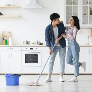 Loving asian couple mopping floor in kitchen