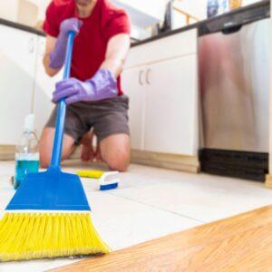 Person using broom on floor