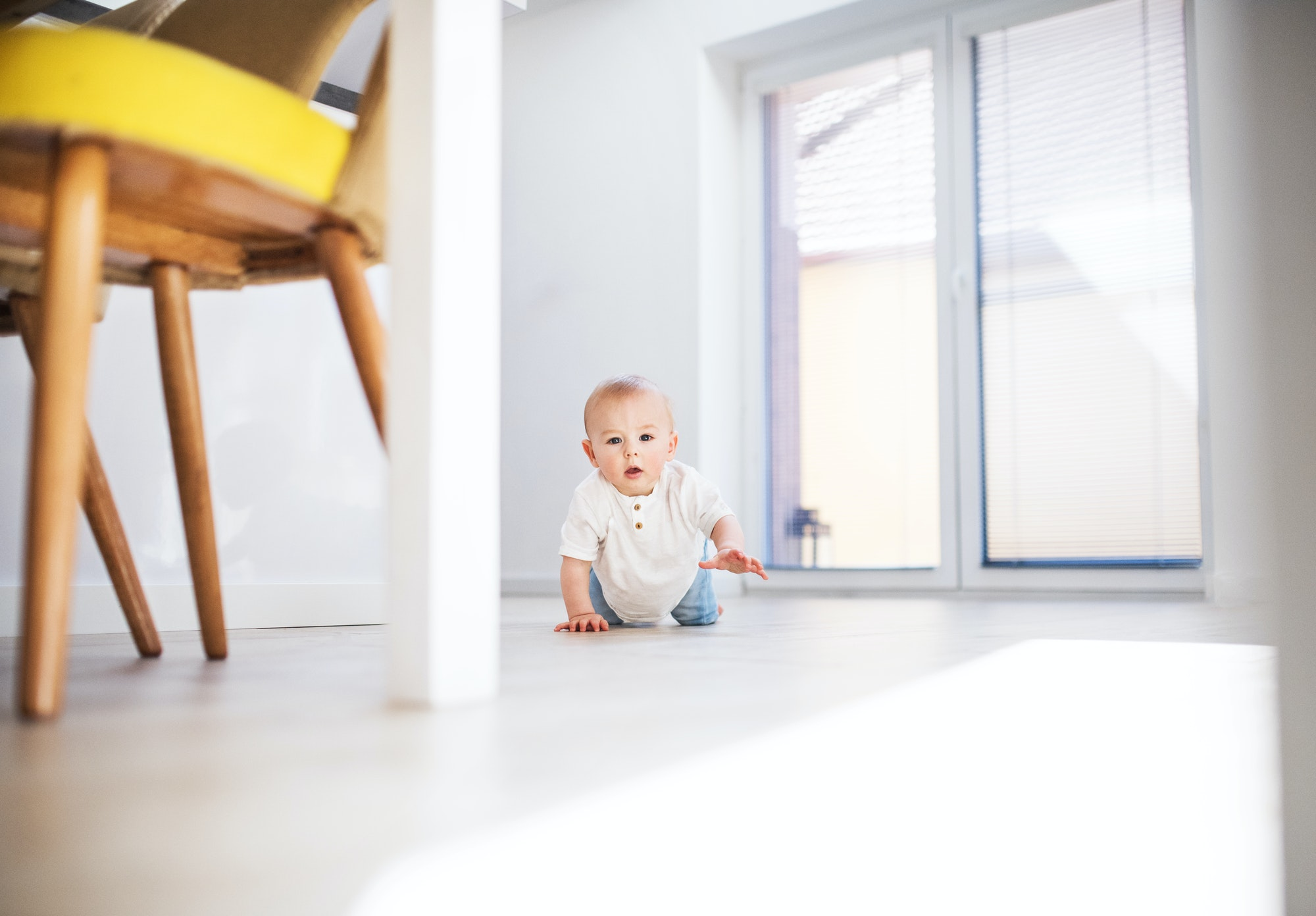 A baby boy crawling on the floor at home.