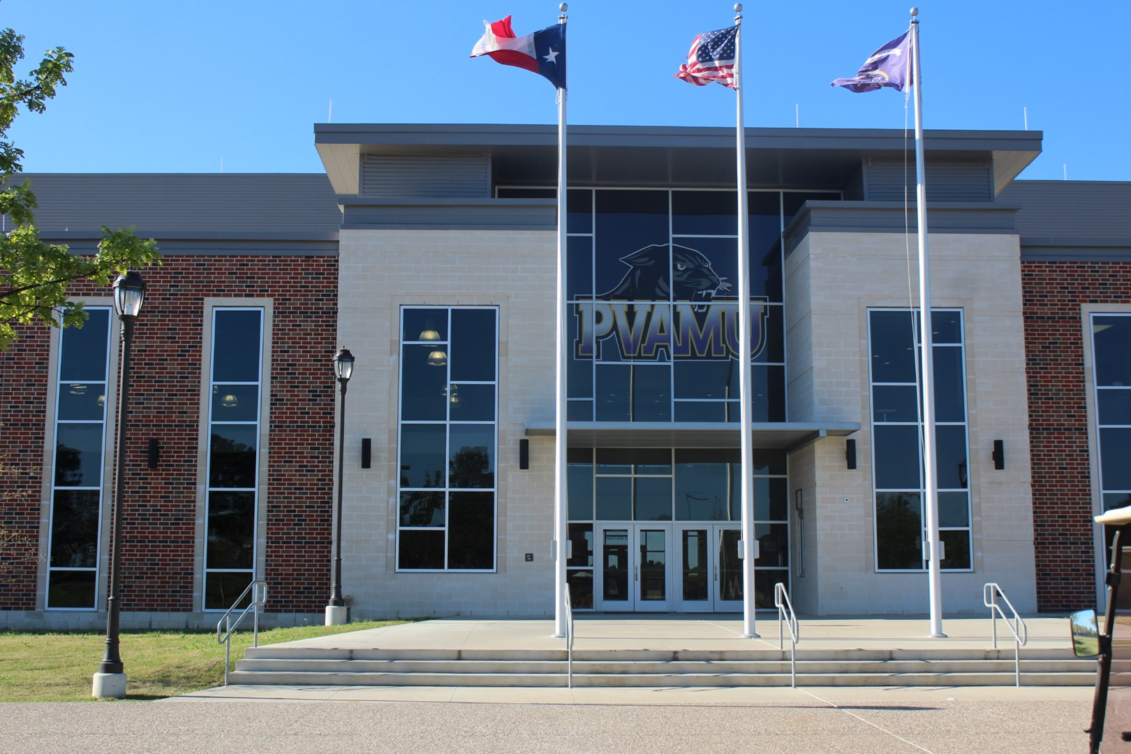 entryway to welcome center at PVAMU and three flag poles
