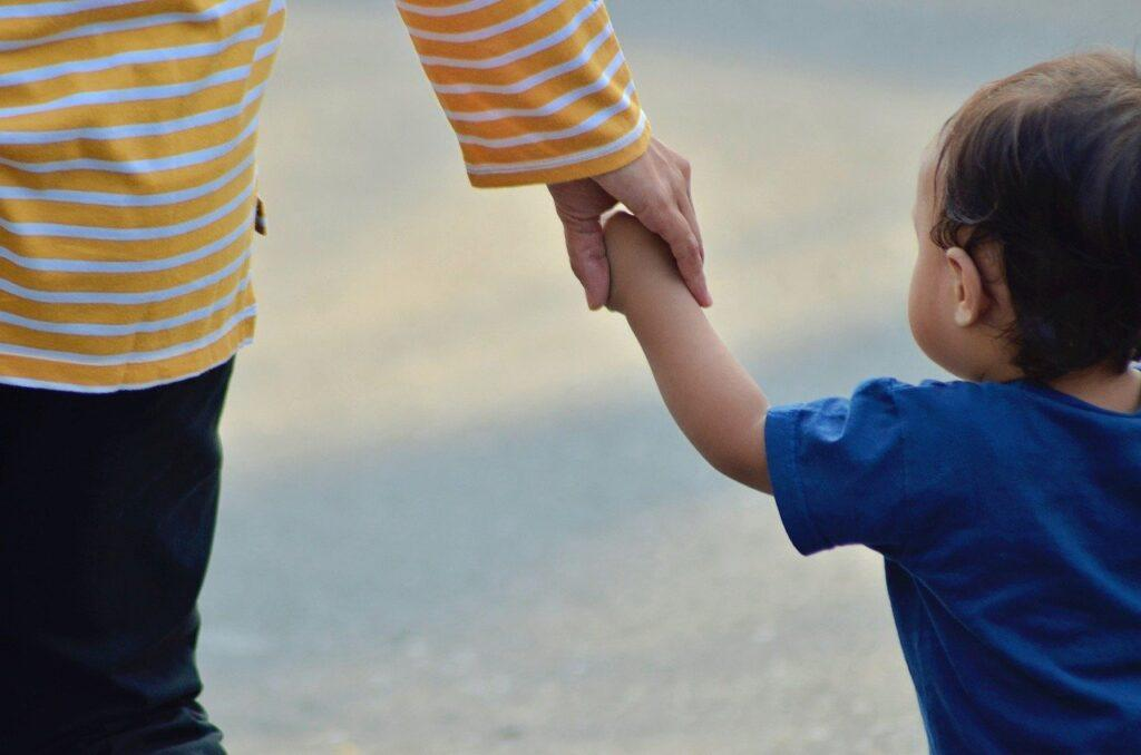 A young child holds their parent's hand as they both walk down the beach.