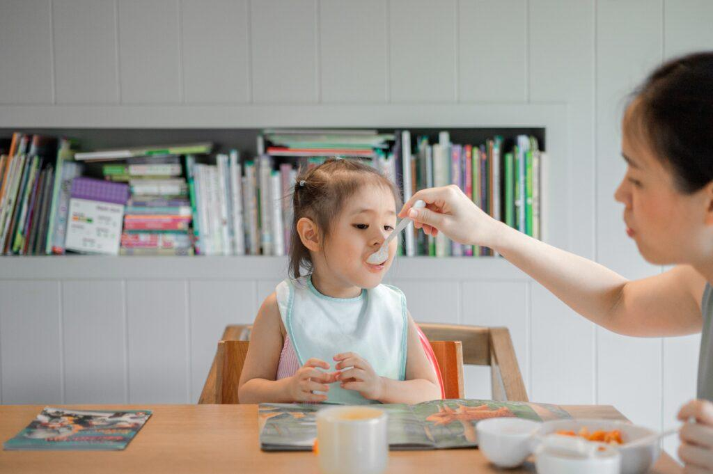 A mother feeds a spoonful of carrots to her toddler.