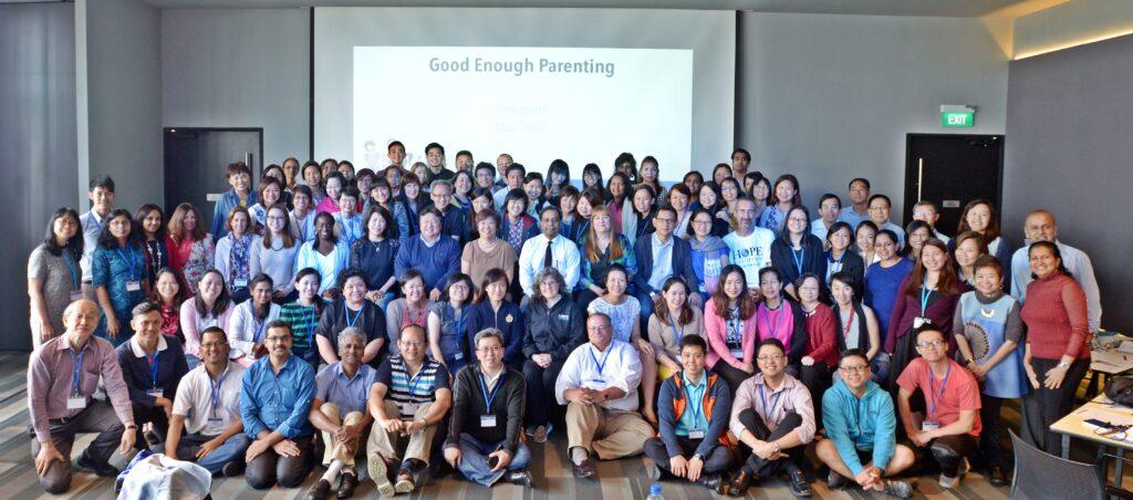 Group photo of about 100 people from various backgrounds at a Good Enough Parenting workshop. Dr. John Louis and Karen McDonald Louis stand at the very center.