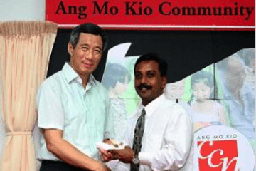 Dr. John Louis receiving the 2005 Comcare Enterprise Fund award from Singapore PM Lee Hsien Loong.