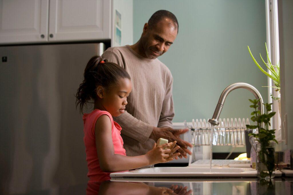 A father and daughter wash their hands in the kitchen sink.