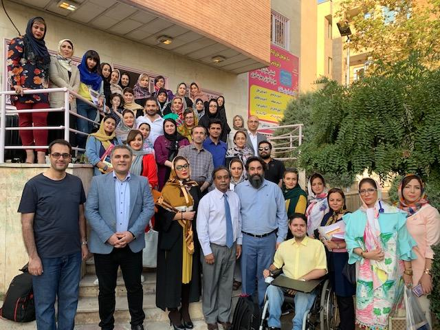 Group photo of several dozen facilitators at a GEP workshop in Iran. Dr. John Louis stands front and center.