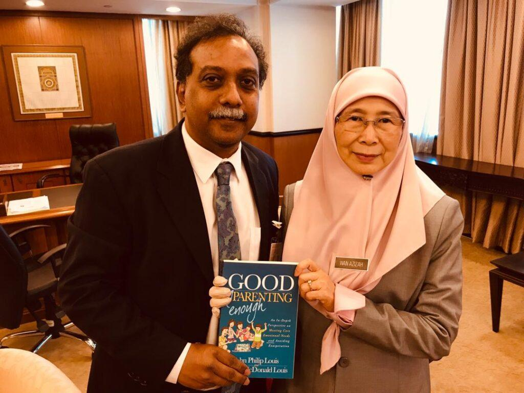 Dr. John Louis holding the first edition of the Good Enough Parenting book with Former Deputy Prime Minister of Malaysia Dato' Seri Dr Wan Azizah binti Wan Ismail.