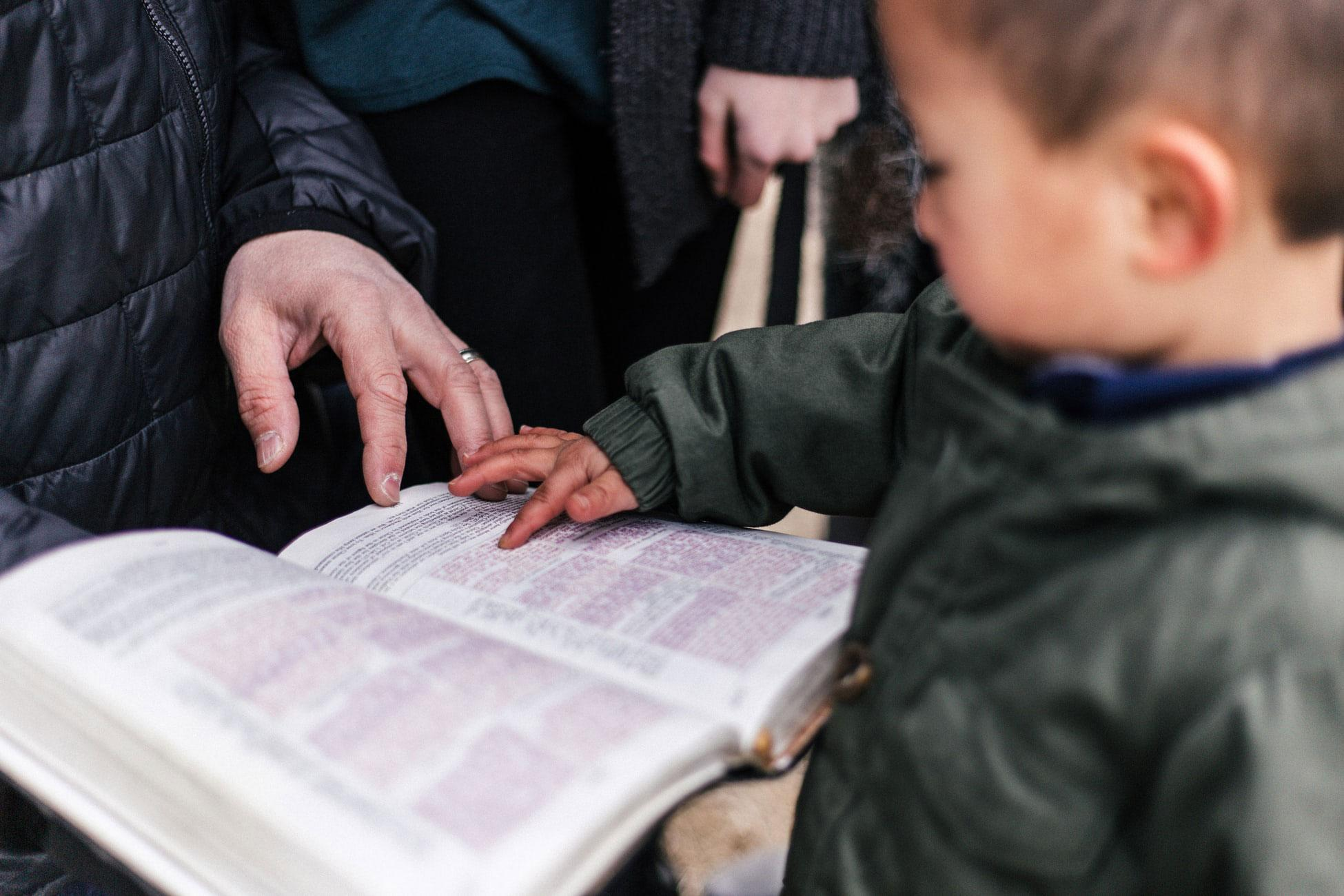 A toddler points at passages in a Bible held by an adult.