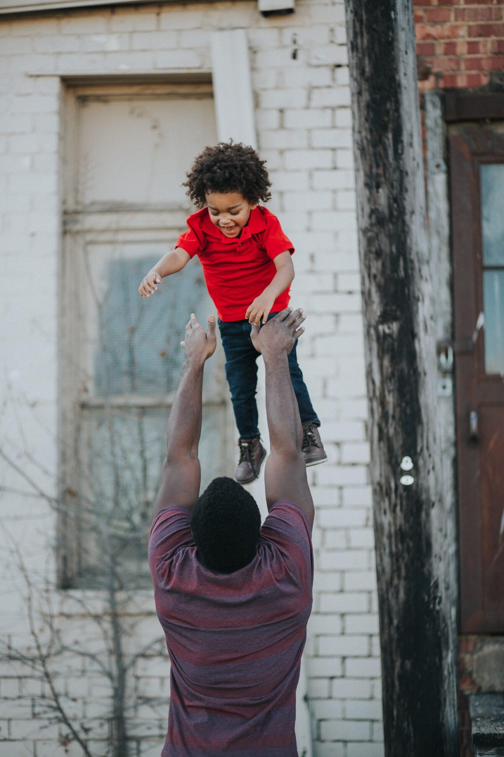 A parent tossing their child in the air.