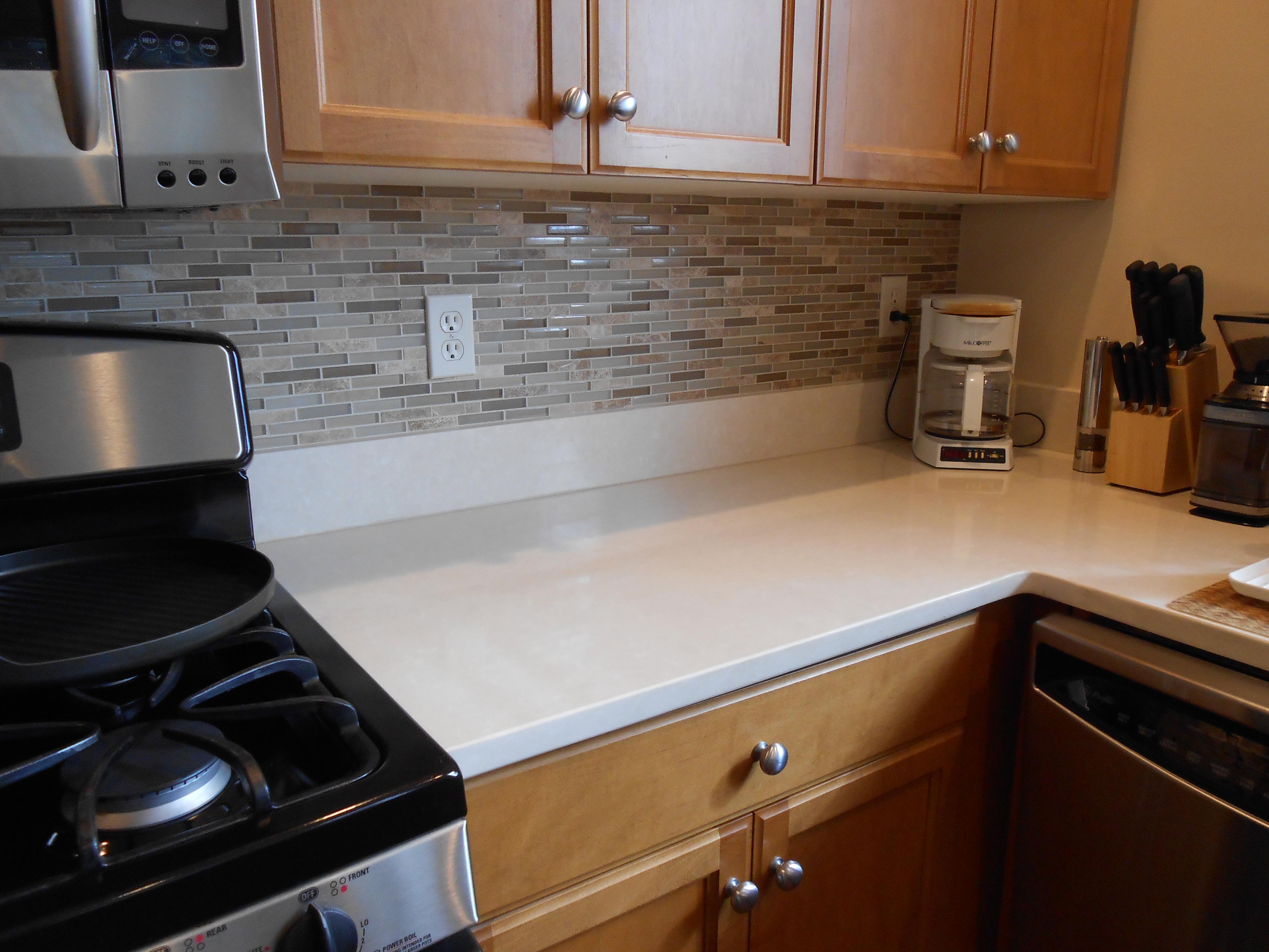 quartz slab countertop and glass tile backsplash