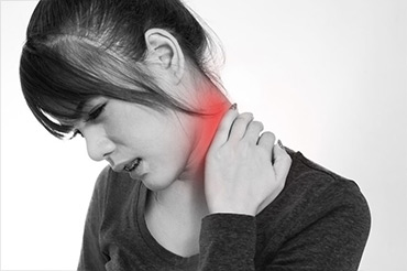 A woman is holding on the back of her neck.