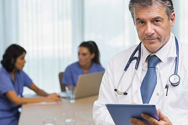 A doctor is keeping a scheduled consultation as two nurses converse in the back.