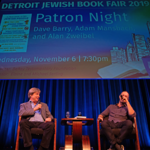 Two speakers with microphones on stage at an event for the Detroit Jewish Book Fair, Patron Night 2019.