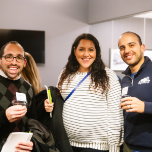 Three attendees of Patron Night 2019 smiling with drinks in their hands.