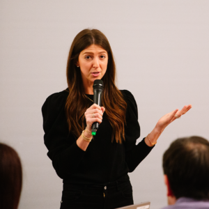 A woman speaking into a microphone in front of a blank white wall at JCC Patron Night 2019.