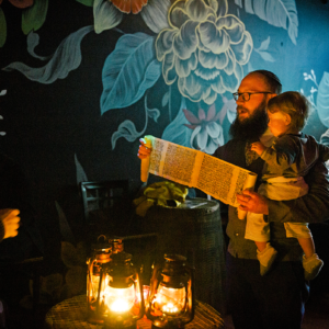 A man reading from a document while holding a baby in a room with painted flowers on the wall.