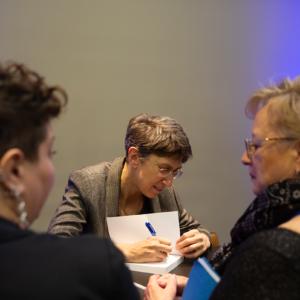 A woman signing a book at the Detroit Jewish Book Fair.