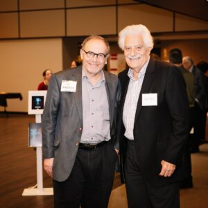 Two patrons smiling at the camera while attending the Lenore Marwil Detroit Jewish Film Festival.