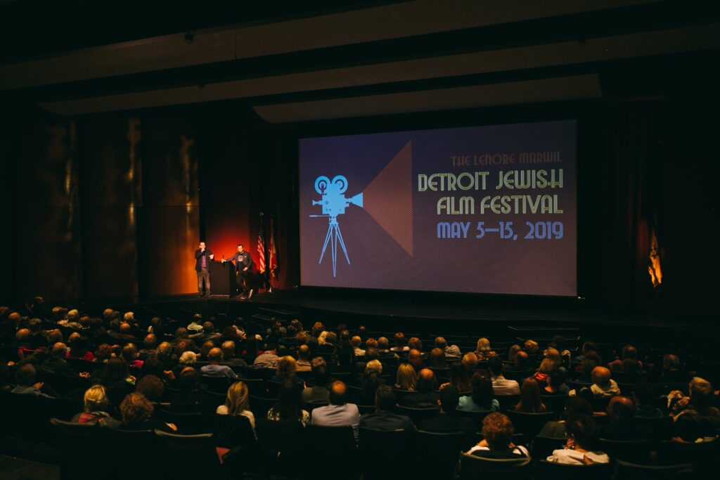 """A packed theatre with two speakers at a podium on the stage and a screen with the words, """"The Lenore Marwil Detroit Jewish Film Festival, May 5-19, 2019."""""""