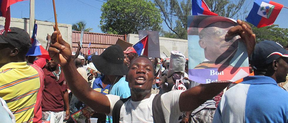 man holding Aristide poster