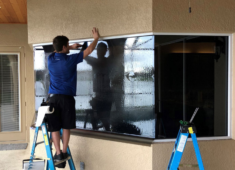 Man on stepladder installing window film on storefront