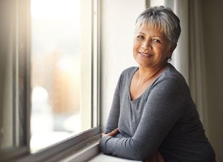 Woman leaning against windowsill enjoying sunshine