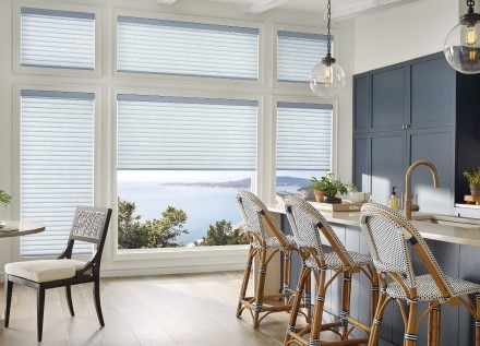 Well-lit kitchen with roller shades over window overlooking waterfront