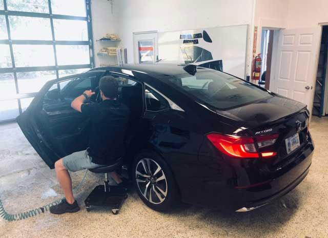 Man installing window tint on a car window