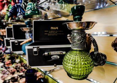 Green Glass Hookah in a Smoke Shop Background