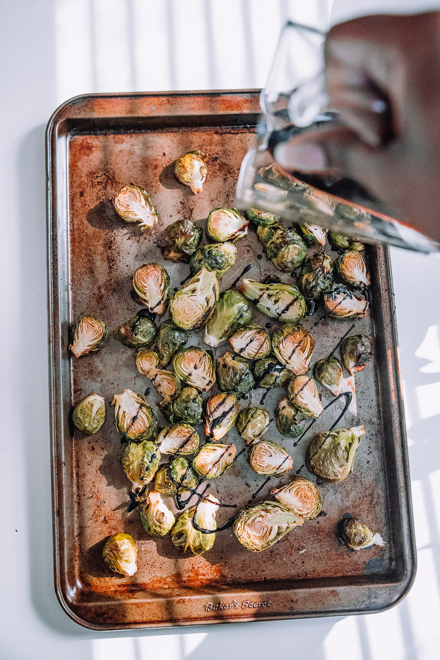 Roasting pan with Brussels Sprouts and balsamic glaze drizzled on top.