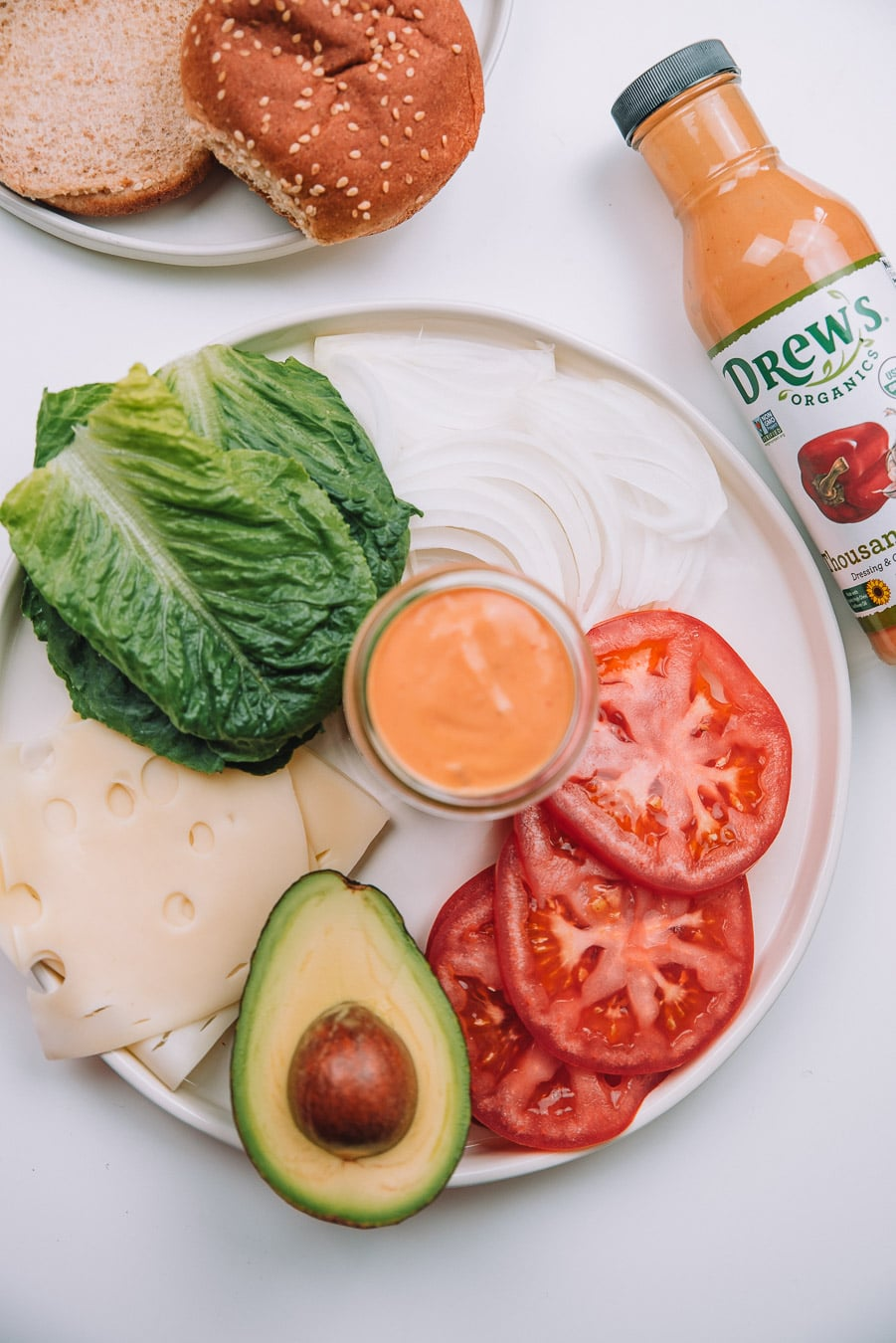 Tomatoes, onion, lettuce, cheese slices, avocado, and thousand island dressing on a plate with a bottle