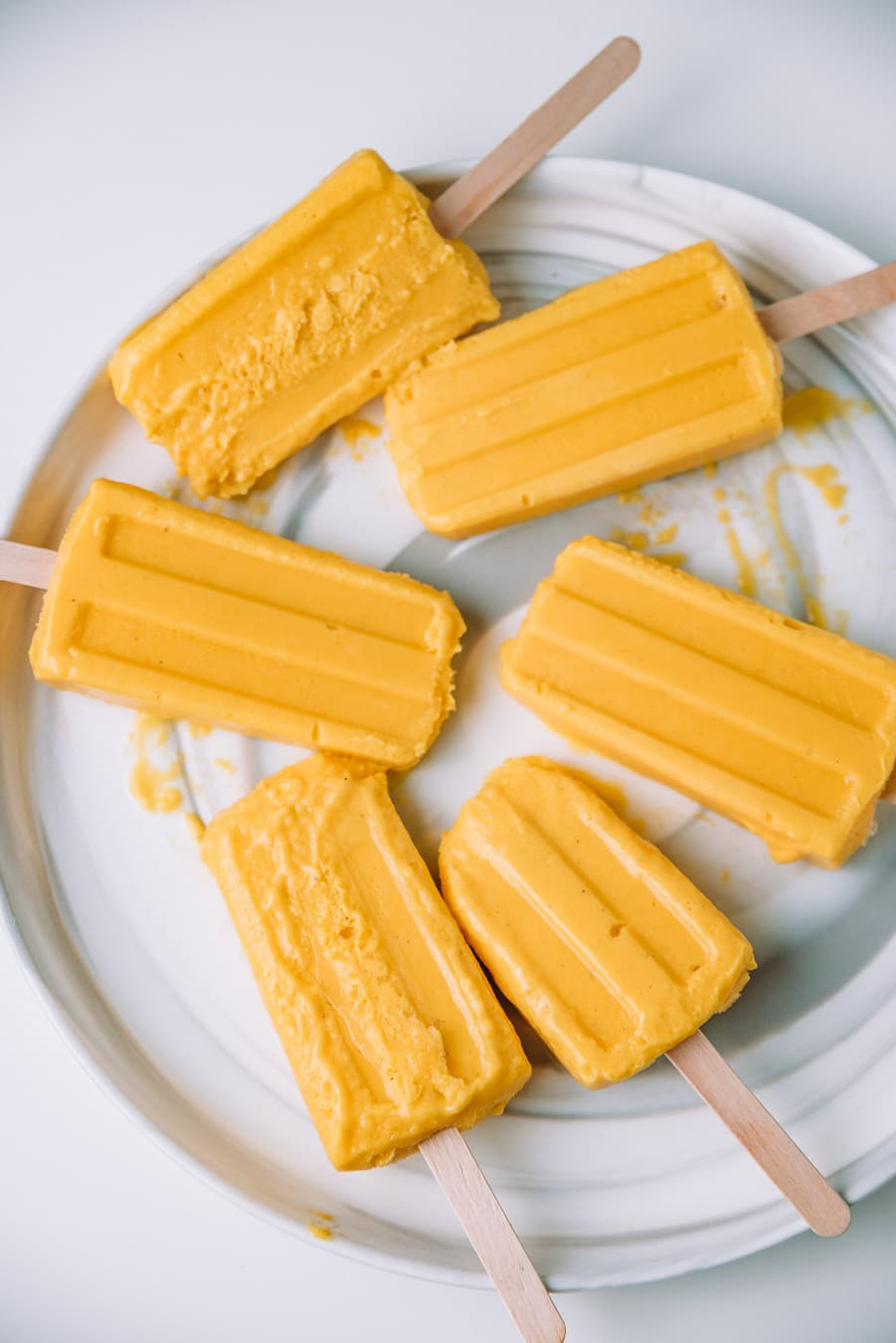 Melting mango lassi popsicles on a plate