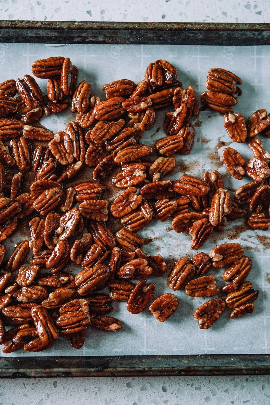 Candied pecans on a parchment lined baking sheet.