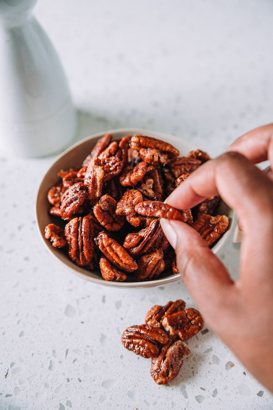 Hand grabbing candied pecans in a bowl.