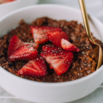 Thick of bowl of chocolate oatmeal with strawberries and chia seeds.